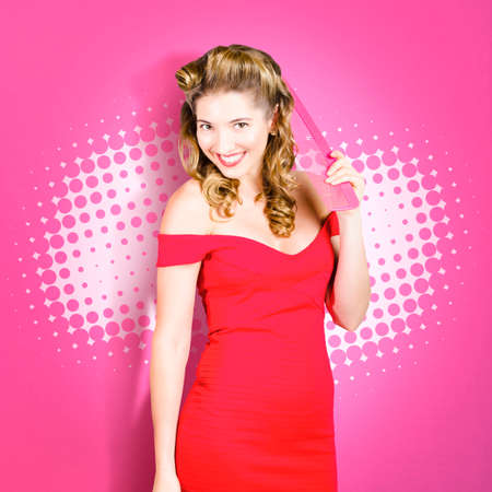 feminine beauty: Feminine beauty and fashion portrait of a beautiful pin up woman in natural makeup and 1960s hairstyle combing blond curls with large pink haircomb. Salon style pin-ups