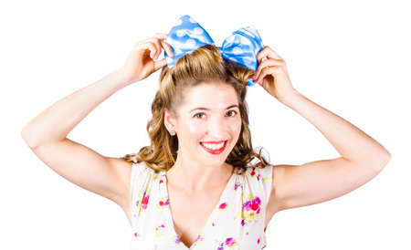 hair tie: Close horizontal photo on the face of a beautiful smiling woman adjusting polka-dot hair tie on sixties rolled hairdo. Retro accessory