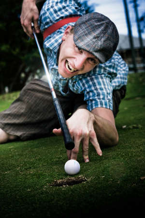 kneel down: Laughing With A Crazy Grin A Mixed Up Sports Man Plays Pool Using His Golf Club As A Snooker Que Aiming For The Greens Hole Stock Photo