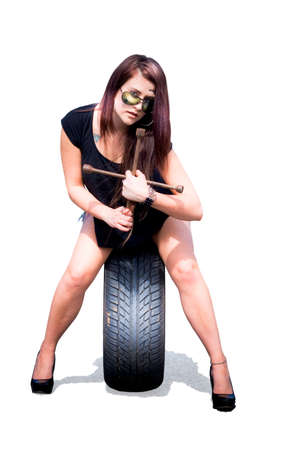 tire service: Isolated Studio Photograph Of A Female Mechanic Holding Tools About To Change A Car Tyre Or Tire In A Automotive Mechanic Parts And Service Concept