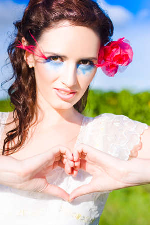 heart hands: Romantic Woman With Beautiful Makeup And Hair Rose Shows A Sign Of True Love By Creating A Heart With Her Hands In A Positive Loving And Tender Outdoor Gesture Stock Photo