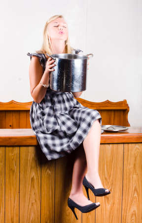 smells: Young, blonde-haired woman sits crosed-legged on countertop and smells aroma from a large cooking pot Stock Photo