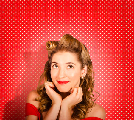 50s fashion: Close portrait on the face of a beautiful young pinup fashion woman wearing retro make-up and classic 50s hairstyle looking up to beauty copyspace. Red polka dot studio background Stock Photo