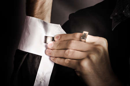 dapper: Dark fashion photograph of a stylish man putting cuff links on his white colored shirt Stock Photo