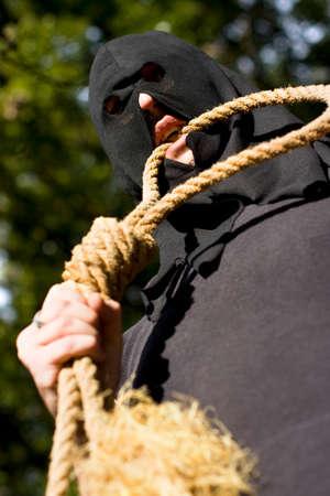 ahorcado: Ahorcado muerde la cuerda para probar la durabilidad de su ahorcamiento del nudo de la soga la horca