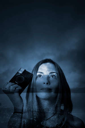 within: Dreamy fine art double exposure on photography woman holding camera on dark blue atmospheric landscape. An ocean between us