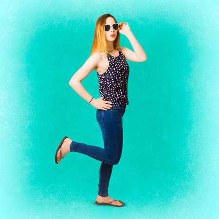 wearing sandals: Fun retro pinup portrait on a eighties style woman stepping back in blue jeans and trendy fashion. Pinup women