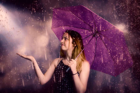 rain weather: Purple toned fine artwork of a beautiful female model feeling the rain during a tumultuous wet weather storm. Sensation and touch Stock Photo