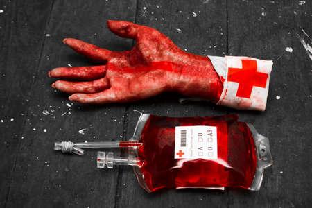 picada: Frakenstein en la fabricación con un monstruo picada mano envuelta en la preparación médica junto a la bolsa llena de sangre para infusión. concepto de Halloween
