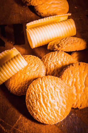 rounds: Rich buttery shortbread rounds, biscuits or cookies in a heap on a wood table with neat coils of fresh farm butter Stock Photo