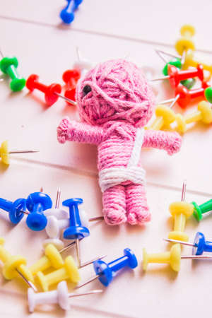 vodoo: Colourful still life on a pink mummy voodoo doll scattered amongst pins and needles. Halloween black magic