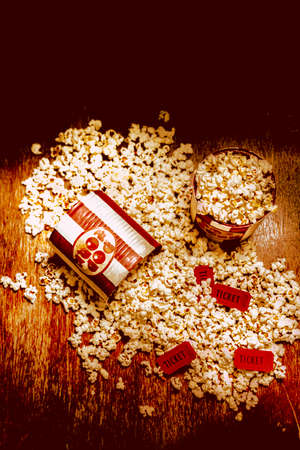 High Angle Still Life View of Popcorn Spilling from Toppled Tubs on Rustic Wooden Table with Red Movie Tickets - Cinema Theater Concept