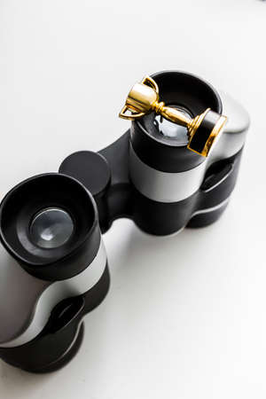 recompense: High Angle View of a Tiny Gold Winners Cup Resting on Top of the Eye Piece on a Pair of Binoculars on White Background. Looking to win