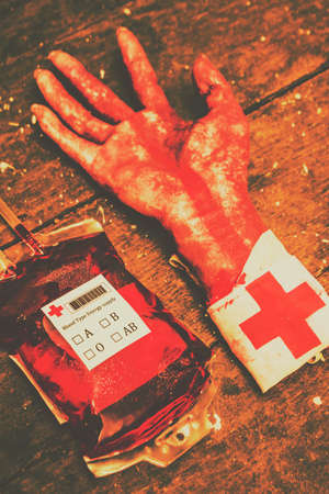 grisly: Halloween Horror Hospital Still Life of a Bag of Blood and Severed Hand with Red Cross Bandage on Wrist Resting on Rustic Wooden Table