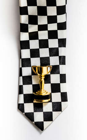 1st place: Small golden cup is on the black and white squared tie. 1st place racing badge Stock Photo