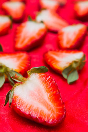 preperation: Various sliced strawberries close up over red background with copy space. Dessert preperation Stock Photo
