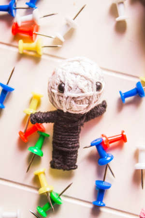 bewitch: Handmade sting voodoo doll laying amongst scatter of pins and needles. Modern black magic Stock Photo