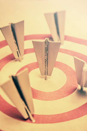 pointed arrows: Metal paper airplane arrow darts to hit right target sign, business aims and smart solutions concept