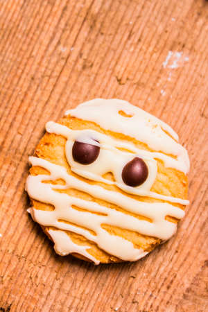 sugar cookie: Single homemade mummy cookie for Halloween with icing sugar bandages and staring chocolate eyes on a wood background with copy space