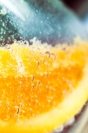 bubbly: Macro detail on a orange slice in clear bubbly cocktail glass. Nightclub beverages Stock Photo