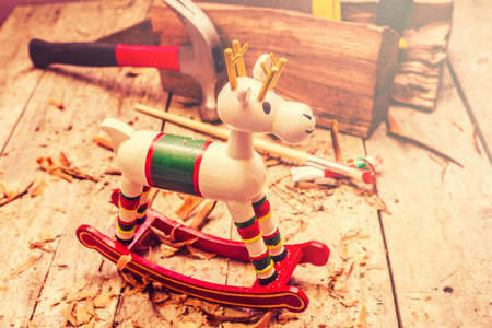 horse sleigh: Close-up of beautiful handmade xmas rocking deer in wooden chips beside tools in christmas workshop Stock Photo