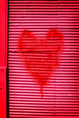 exterior shape: Passionate red heart for a Valentines sweetheart symbolic of love and desire spray painted on a vivid red metal wall Stock Photo
