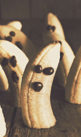 resemble: Healthy rustic trick-or-treat Halloween snacks with halved fresh ripe bananas decorated with chocolate eyes and mouths to resemble ghosts or ghouls on a shadowed creepy background Stock Photo