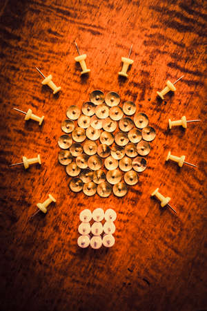 plastic material: Light beaming on brass and plastic material pushpins arranged on wooden office desk. Corporate lightbulb icon Stock Photo