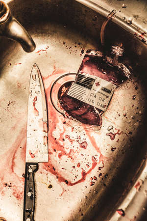 Spoiled blood bag with knife and lot of blood spilled in contaminated stainless steel sink, halloween concept Editorial