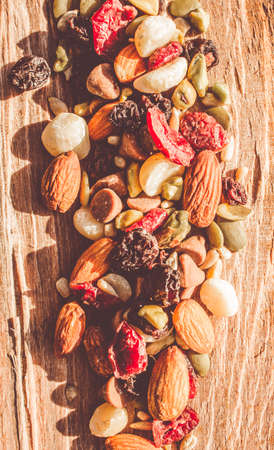 dried food: Rustic country food artwork on a mix of dried fruits, nuts, seeds and chocolate on wooden bench