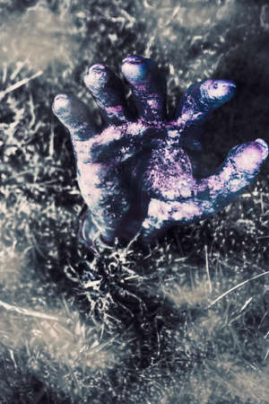 hand raising: Spooky halloween image of a dead zombie hand raising hell when rising from the grave. Terror from the crypt