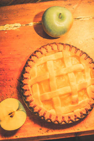 pastry crust: Grandmas homemade apple tart with fresh whole and halved green cooking apples and a golden pastry crust viewed from above on wood