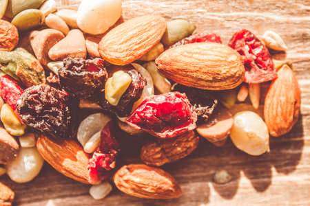 energy mix: Trail mix high-energy snack food background with a nutritious mixture of nuts, seeds, kernels, dried fruit and chocolate on a wooden surface in a close up view