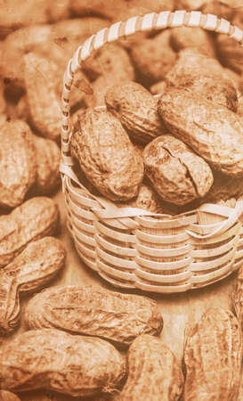 weaker: Closeup toned image of peanuts in small wicker basket. Groundnuts still-life