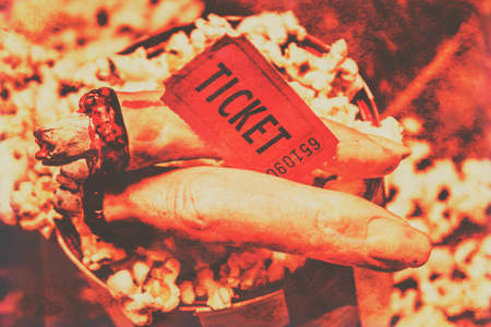 slasher: Concept Still Life of Halloween Horror Film Event - Severed Fingers Holding Movie Ticket on Top of Bag of Theater Popcorn