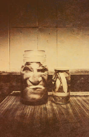 grisly: Vintage Halloween Decorations - Severed and Preserved Head and Hand in Jars of Liquid on Rustic Wooden Table