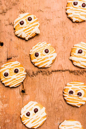 messily: Rustic home cooking still life on a pile of messily decorated monster mummies made with melted white chocolate on shortbread base Stock Photo