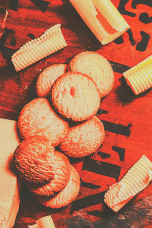 crumbly: Vintage red toned rich butter shortcake cookies or crumbly biscuits with neat coiled rolls of fresh farm butter scattered on an old packing crate with lettering from a label, overhead view