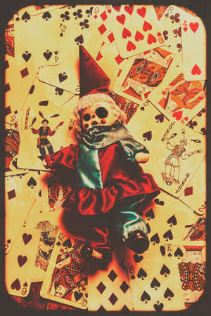 Spooky evil clown toy doll on scattered casino playing cards background, black magic and fortune telling