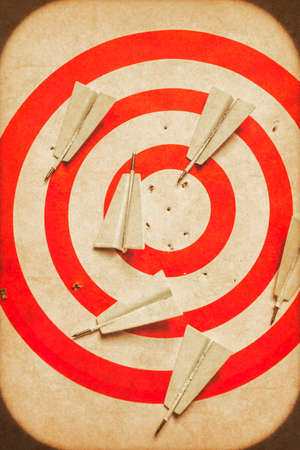 target practice: Red and white old tin dartboard with several paper plane darts placed amongst a scattering of holes. Business target practice Stock Photo