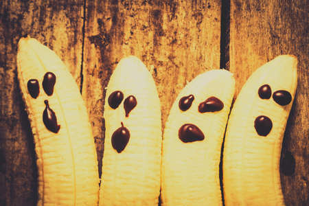 chocolate treats: Comical vintage still life food photo on four halloween ghost bananas with looks of chocolate terror. Halloween healthy treats Stock Photo