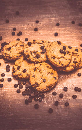 choco chips: Pile of freshly baked delicious crunchy homemade cookies with choco chips topping on wooden surface Stock Photo