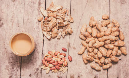 monkey nut: Pile of fresh whole peanuts, shells, raw nuts and peanut butter in a jar conceptual of production and preparation of the final product, overhead view