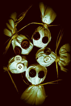 spectre: Five Halloween dolls with button eyes with heads close together in a circule over dark background. Trick or treaters