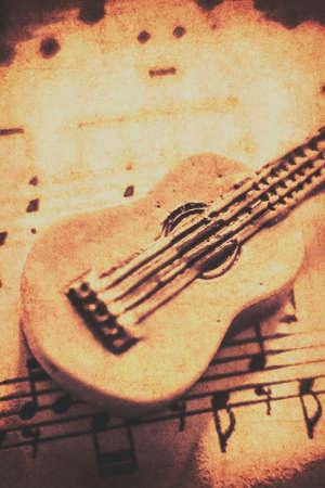 single songs: Sepia toned weathered close up on single little carved guitar on sheet music. Folk songs