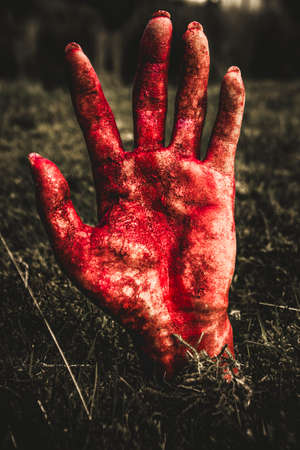 Frightening picture of womans blood stained hand pushing up cemetery dirt at graveyard. Fright night terror