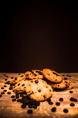 choc: Rustic home cookery still-life on  Freshly Baked Crispy Choc Chip Biscuits Arranged on Wooden Table Surface Surrounded by Chocolate Chips in front of Dark Brown Background with Copy Space