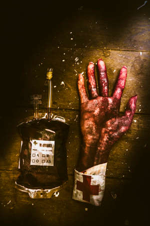 Horror hospital concept on a severed arm with blood bag lying on wooden background. Frankenstein transplant experiment