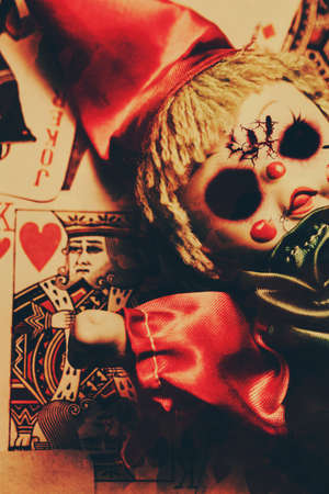 horrifying: Closeup of cracked old broken doll dressed as joker on playing card with picture of king