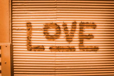 vandalize: Orange grunge graffiti design on urban metal garage wall. Love in words Stock Photo